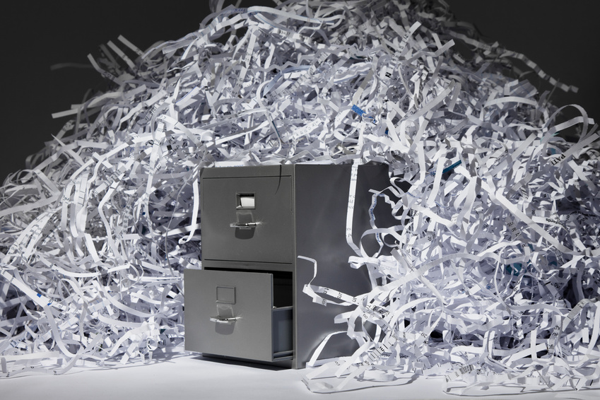 pile of shredded documentation on top of a gray filing cabinet